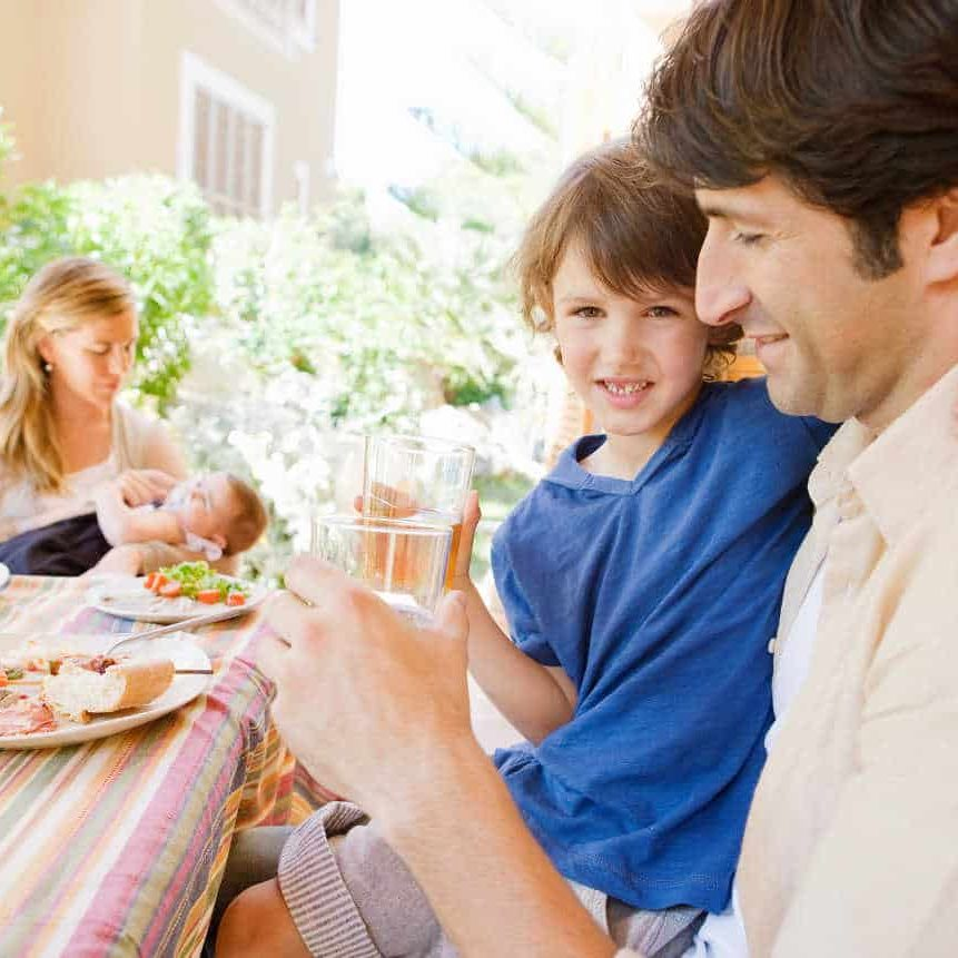 Family of four gathering around a table with food in a home porche garden outdoors with mother, father, baby girl, and a young boy drinking water with dad.