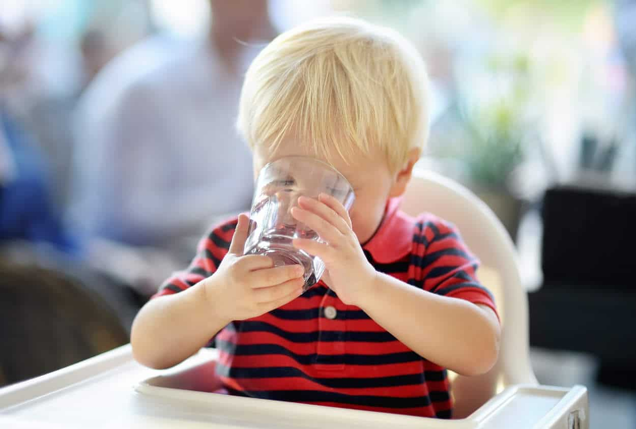 Adorable toddler boy drinking water in outdoors cafe