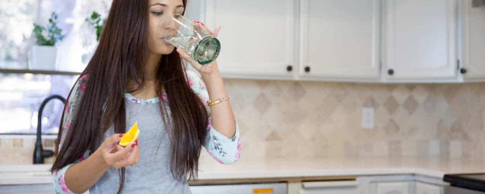 Beautiful brunette drinking purified water from her tap water from glass at the kitchen.
