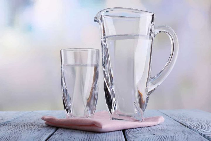 Glass pitcher and glass of water on wooden table on bright background. The water was purified via a reverse osmosis system for drinking water in Chandler AZ